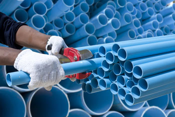 New Jersey Water Pipe Repairs, Worker cut pvc pipe in construction site